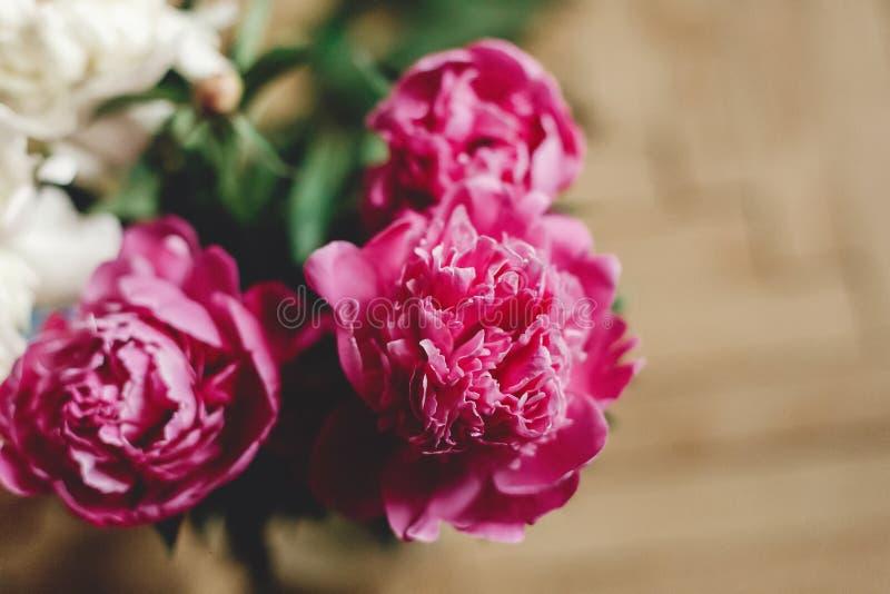 Härlig rosa och vit pionbukett i exponeringsglaskrus på det lantliga trägolvet, framlänges som är lekmanna- Blom- dekor och ordni royaltyfria foton