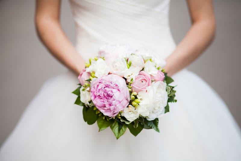 Härlig rosa pionbröllopbukett i bruds händer, closeup royaltyfria foton