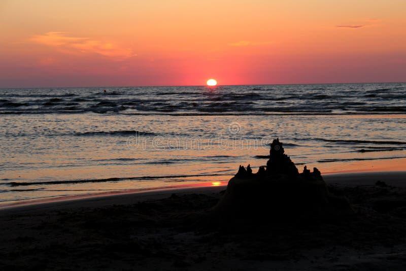 Härlig rosa solnedgång med ett solspår och en sandslott i förgrunden arkivbild