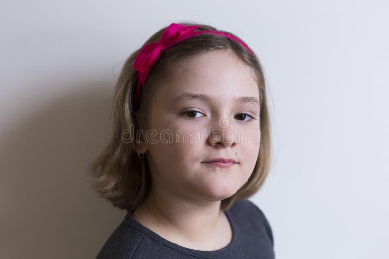 Härlig runda-vänd mot ganska liten flicka med uppnosigt uttryck royaltyfria bilder