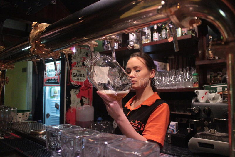 Härlig rysk flicka som fyller ett exponeringsglas med öl i en stång i Almaty fotografering för bildbyråer