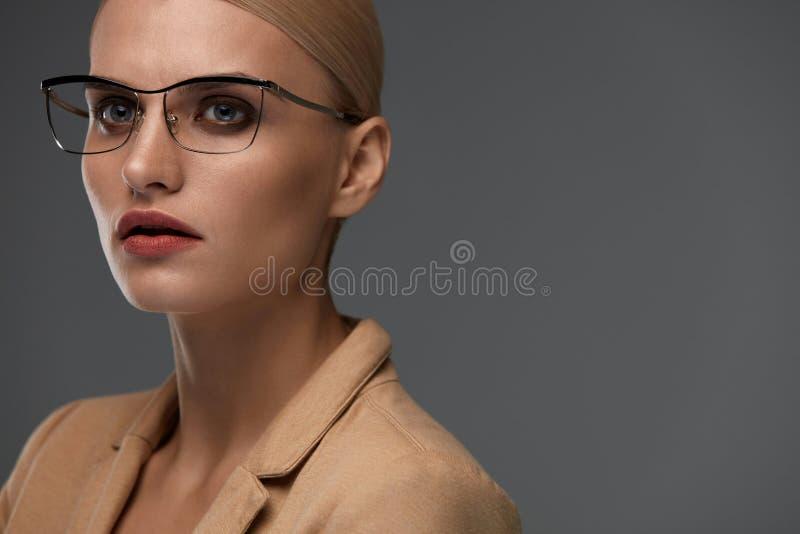 Härlig säker affärskvinna i modeexponeringsglasstående royaltyfri fotografi