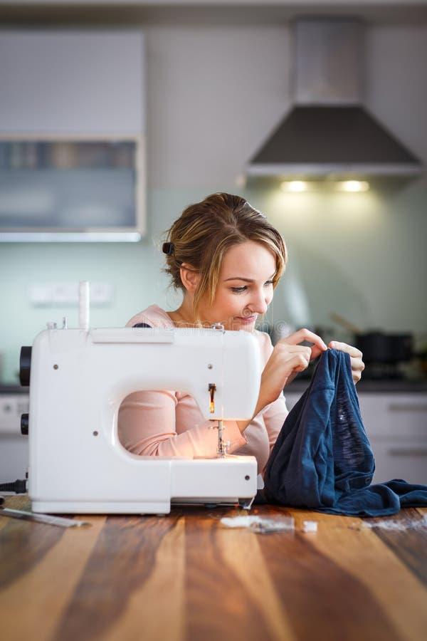 Härlig sömnadkläder för ung kvinna med symaskinen royaltyfria bilder