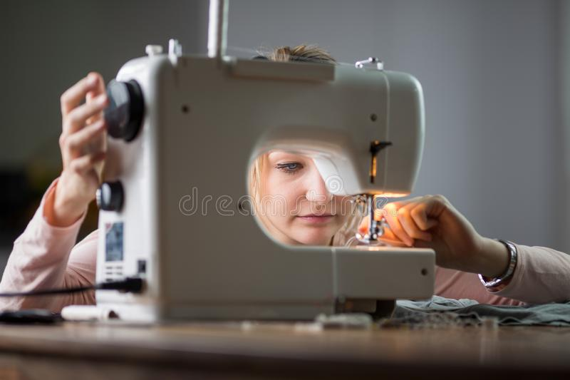 Härlig sömnadkläder för ung kvinna med symaskinen arkivbild