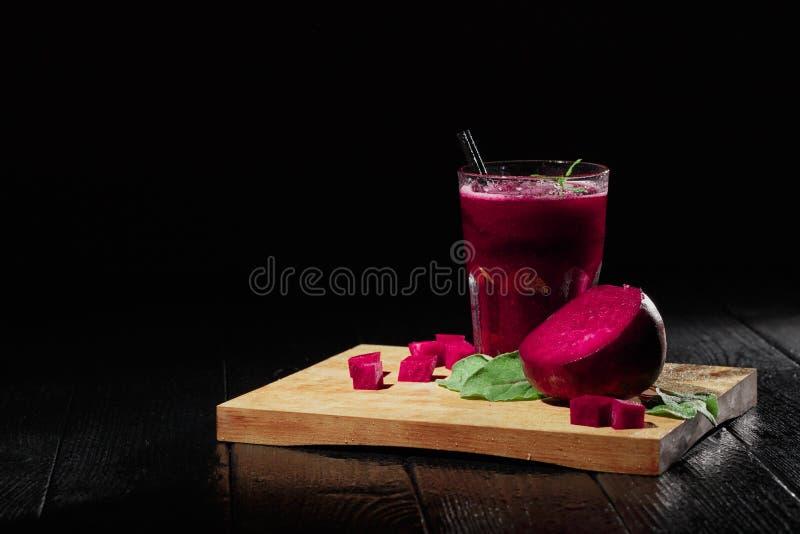 Härlig sammansättning av veggiedrinken Betasmoothie och klippt rödbeta på en svart bakgrund Betaprodukter kopiera avstånd arkivfoton