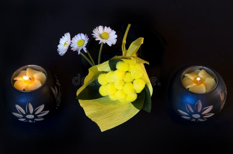 Härlig sammansättning med den tända etniska stearinljus, tusenskönor och mimosan på en svart bakgrund royaltyfri bild