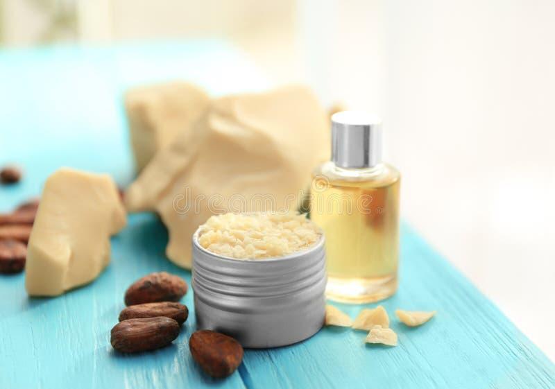 Härlig sammansättning med ingredienser för lotion för kakaosmör på tabellen royaltyfri fotografi