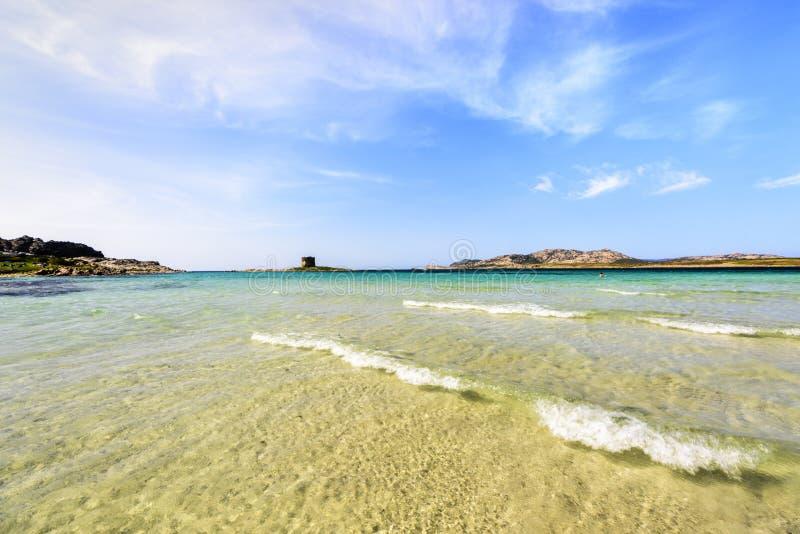 Härlig sandstrand med mjuka vågor mot blå himmel med moln - LaPelosa strand med det lilla tornet i bakgrunden, Sardinia arkivbilder