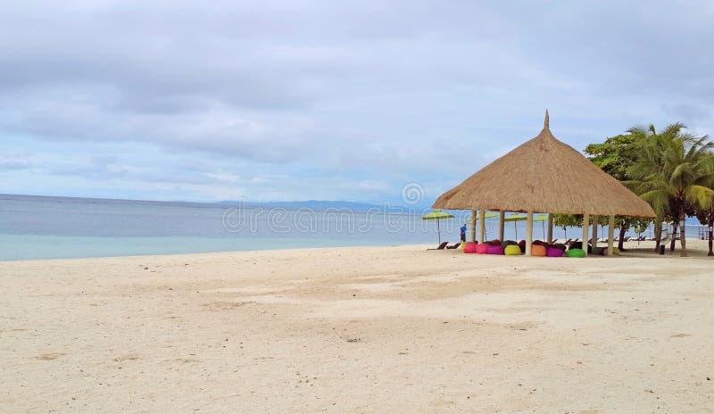Härlig seascape av den vita sandstranden med färgrika platser i den trevliga gazeboen i molnig dag på den Bohol ön, Filippinerna royaltyfria foton