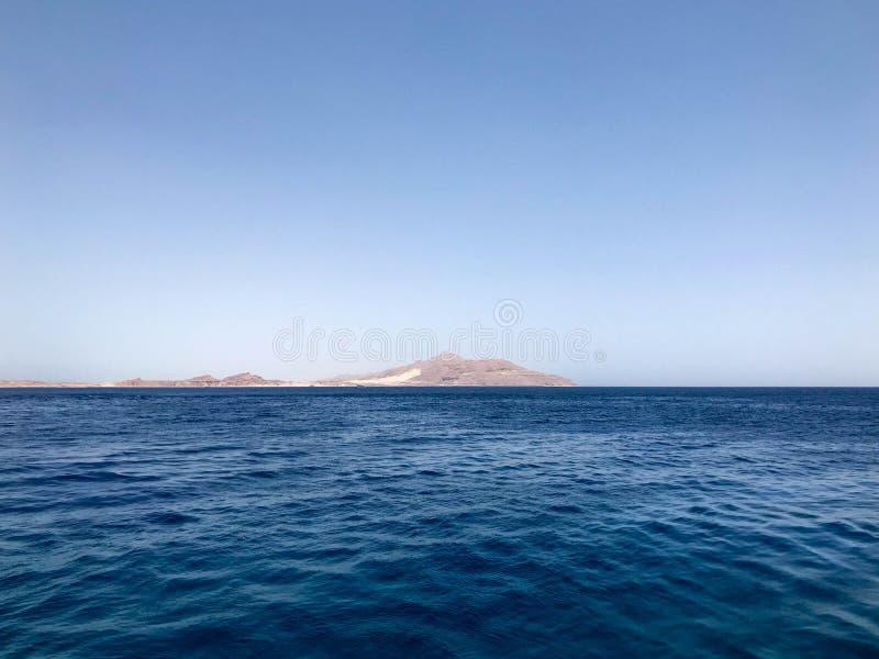 Härlig seascape som förbiser det blåa salta havet, gula sandiga berg på den tropiska badorten royaltyfria foton