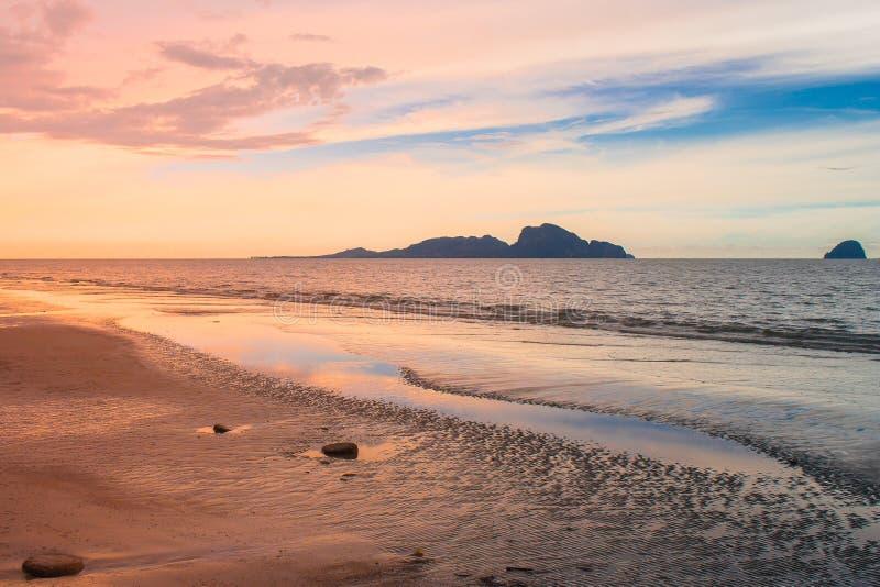 Härlig seascapesikt av sandstranden med havet och ön i bakgrunden på skymningtid fotografering för bildbyråer