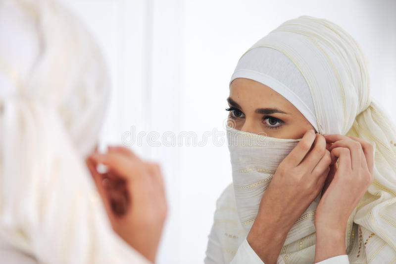 härlig seende spegelmuslimkvinna arkivfoton