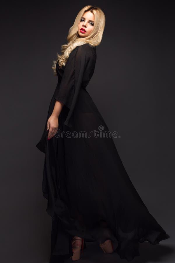 Härlig sexig blond flicka med sinnliga kanter, modehår, svart klänning Härlig le flicka arkivfoton