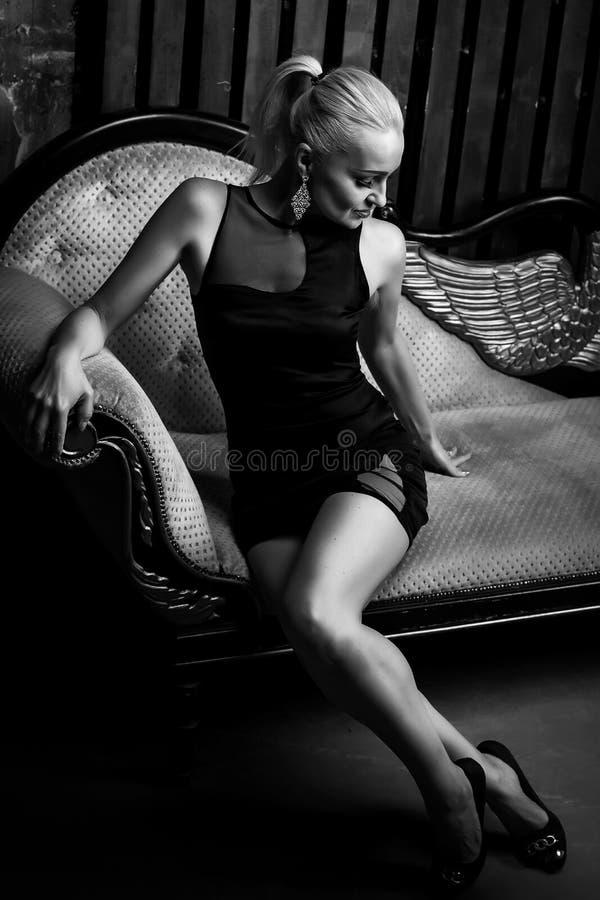 Härlig sexig blond kvinna i kort svart klänning royaltyfri fotografi