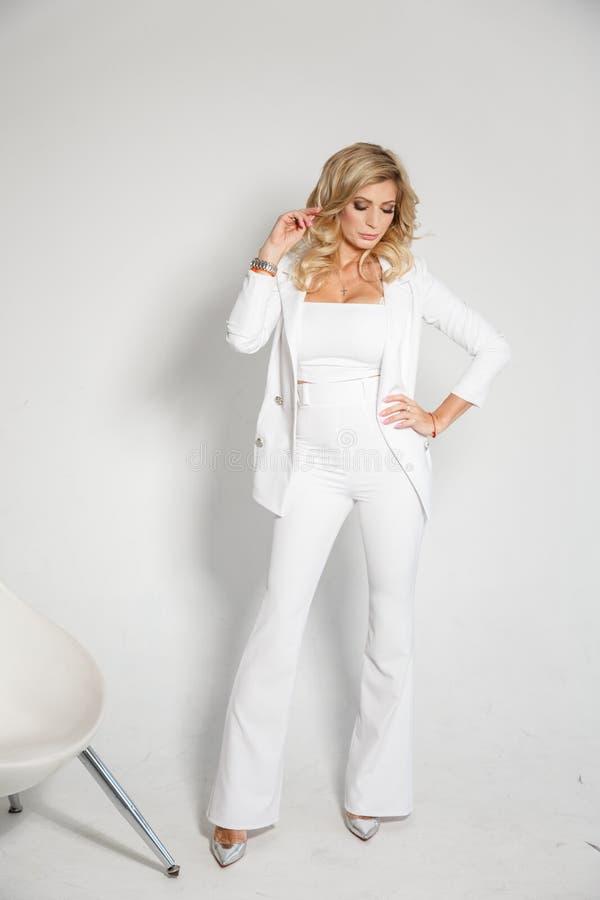 Härlig sexig blondin i en vit dräkt som poserar på vit bakgrund arkivbild