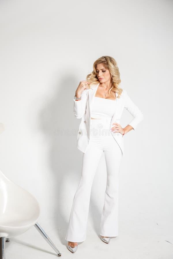 Härlig sexig blondin i en vit dräkt som poserar på vit bakgrund royaltyfri bild