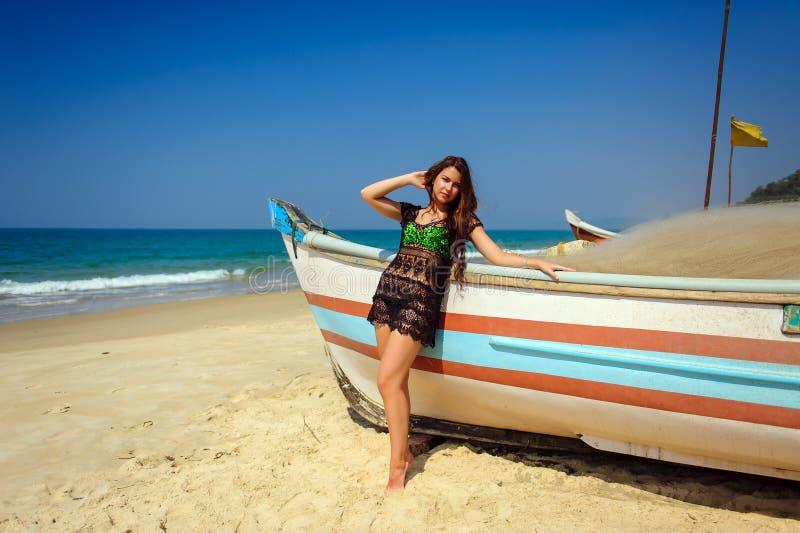 Härlig sexig brunett på den tropiska sandiga stranden nära träfartyget på blå havsbakgrund och klar himmel på varm solig dag royaltyfri bild