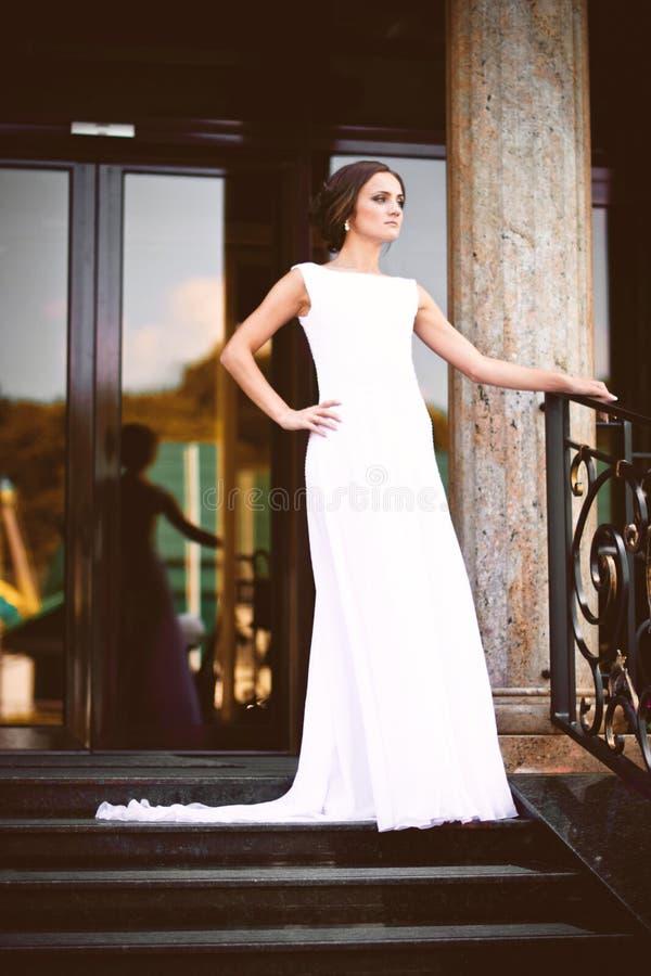 Härlig sexig brunettbrud i den vita klänningen som går upp trappa arkivbild