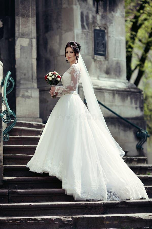 Härlig sexig brunettbrud i den vita klänningen som går upp trappa, royaltyfri foto