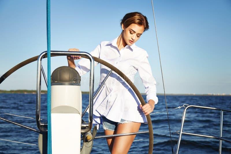 Härlig sexig brunettflicka i yacht för tur för klänningmakeupsommar arkivfoton