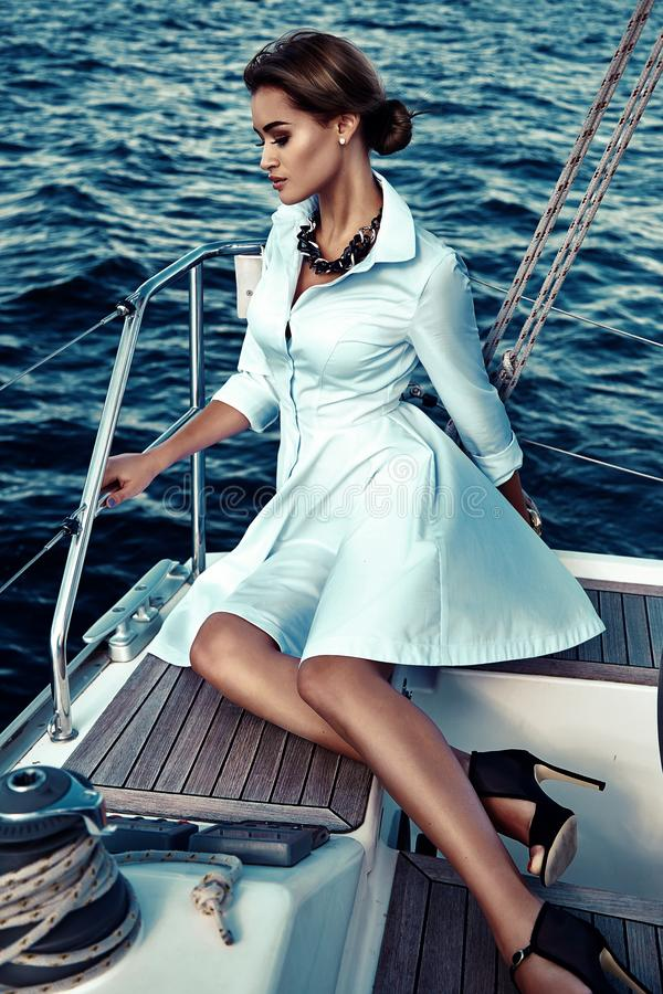 Härlig sexig brunettflicka i yacht för tur för klänningmakeupsommar arkivfoto