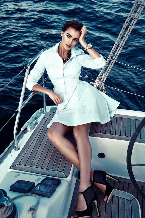 Härlig sexig brunettflicka i yacht för tur för klänningmakeupsommar royaltyfri bild
