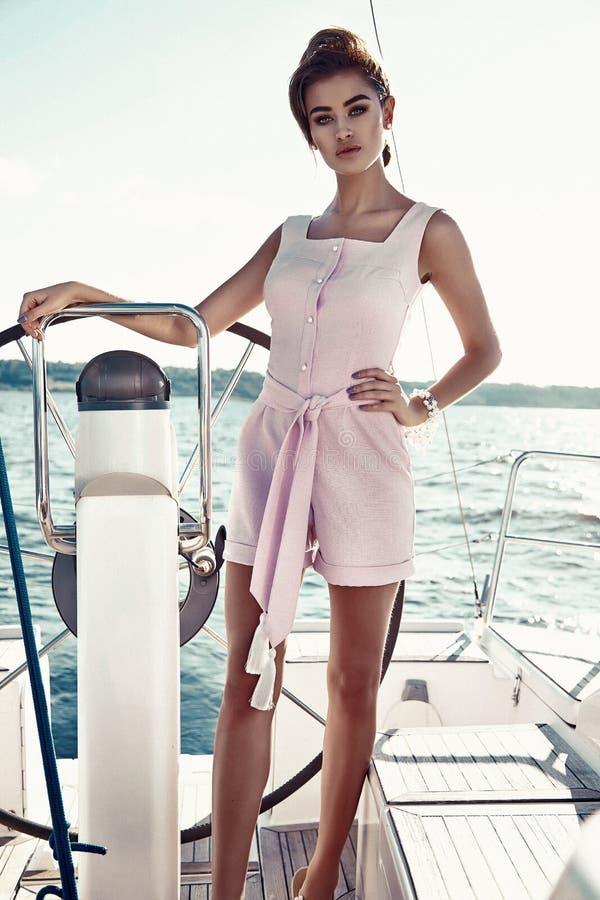 Härlig sexig brunettflicka i yacht för tur för klänningmakeupsommar fotografering för bildbyråer