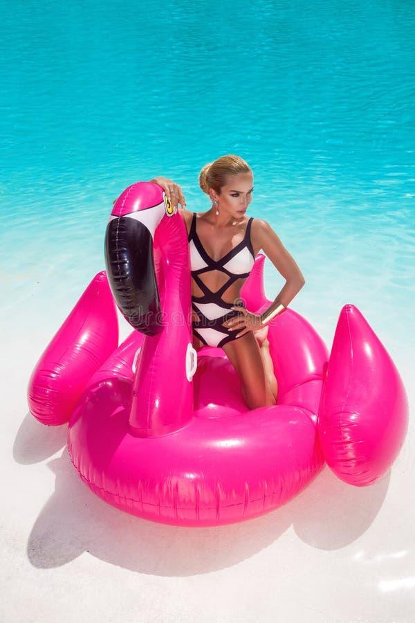 Härlig sexig fantastisk ung kvinna i en simbassäng som sitter på ett uppblåsbart rosa flammande och skrattar, brunbränd kropp, lå arkivfoto