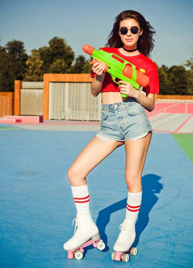 Härlig sexig flicka för stående som poserar på ett tappningrullskridskorderby i grov bomullstvillkortslutningar, den vita T-tröja arkivfoton