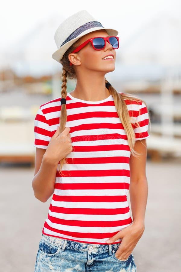 Härlig sexig flicka i kortslutningar och randig t-skjorta, i solglasögon, i hatt, utomhus Brunbränd kvinna i sommar royaltyfri bild