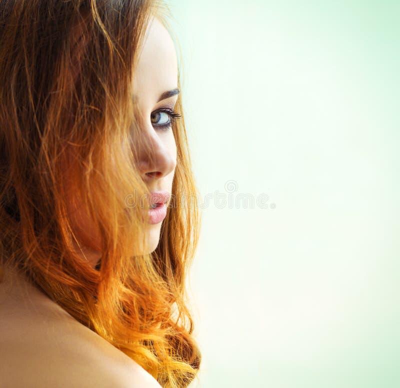 Härlig sexig flicka med långt rött hår med gröna ögon som ut ser över skuldran på en vit bakgrund royaltyfria foton