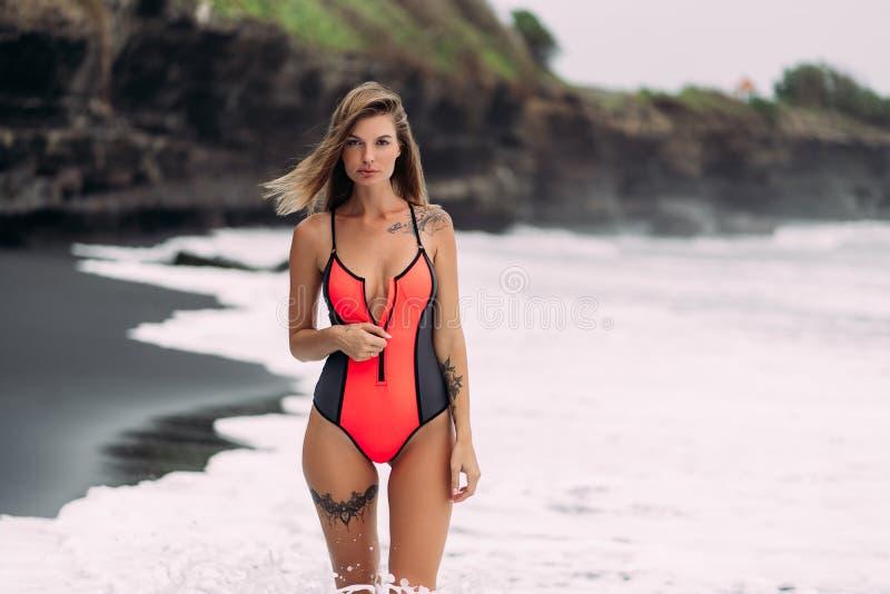 Härlig sexig flicka med stora bröst i en röd baddräkt som solbadar på den svarta sandstranden arkivbilder