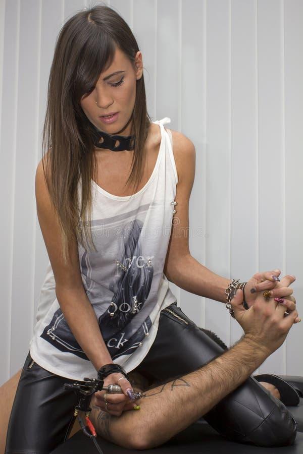 Härlig sexig flickatatuering och innehav en mans hand royaltyfri bild