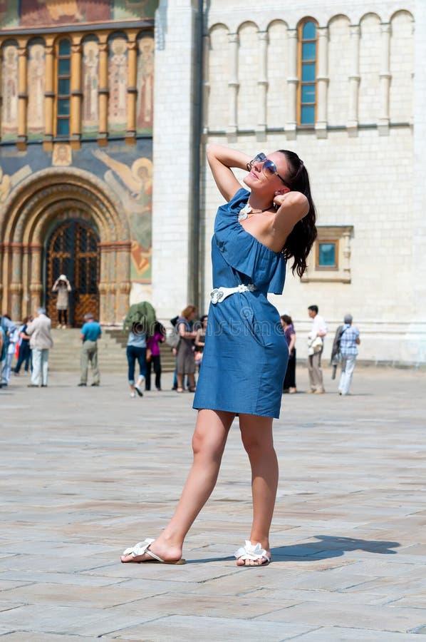 Härlig sexig kvinna i stilfull blå klänningstilkläder för en mötande promenad till och med sommarstaden arkivbilder