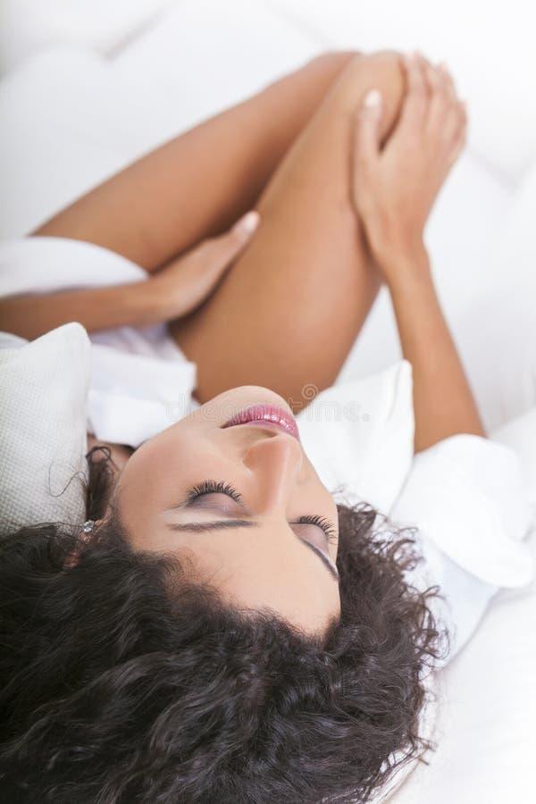 Härlig sexig kvinna i vit säng arkivbilder