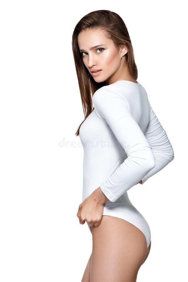 Härlig sexig kvinna med den perfekta kroppen i den vita bodysuiten arkivbild
