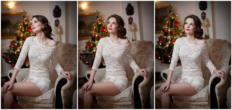 Härlig sexig kvinna med Xmas-trädet i bakgrundssammanträde på elegant stol i hemtrevligt landskap Stående av flickan som poserar  royaltyfri foto