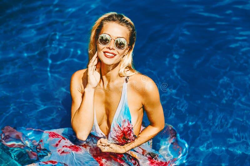 Härlig sexig kvinna som kopplar av i simbassängen som tycker om semester royaltyfri fotografi
