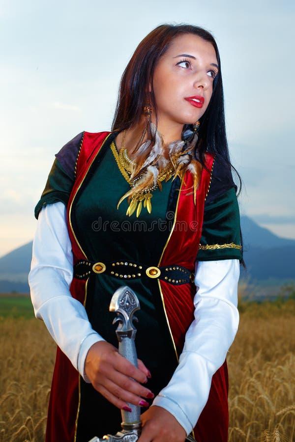 Härlig sexig kvinnakrigare med svärdet Landbakgrund royaltyfri fotografi