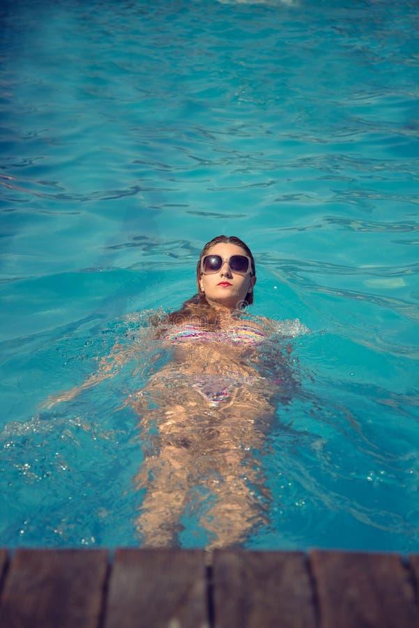 Härlig sexig kvinnasimningbak i perfekt bärande solglasögon för ett blått vatten arkivfoto
