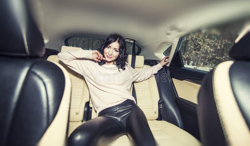 Härlig sexig kvinnlig modell i interien för baksäteläderbil arkivbild