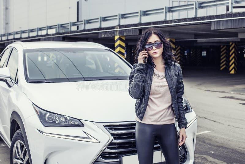 Härlig sexig kvinnlig modell i läderkläder med en vit bil arkivbild