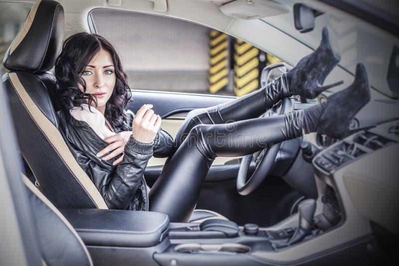 Härlig sexig kvinnlig modell med en vit bil i parkeringsplatsen arkivfoto
