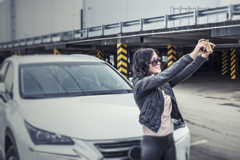 Härlig sexig kvinnlig modell med mor för en vit bil och för en smartphone arkivbild
