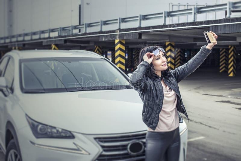 Härlig sexig kvinnlig modell med mor för en vit bil och för en smartphone royaltyfri bild