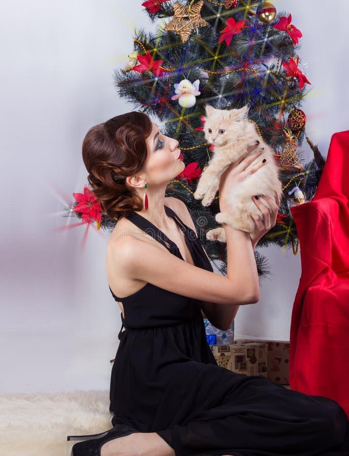 Härlig sexig lycklig le ung kvinna i aftonklänning med ljus makeup med röd läppstift som sitter vid julgranen royaltyfri fotografi