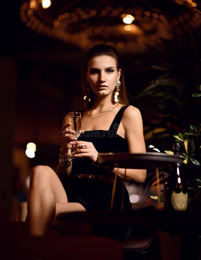 Härlig sexig modebrunettkvinna i dyr inre restaurang som dricker champagne som väntar på det mörka kafét royaltyfria foton
