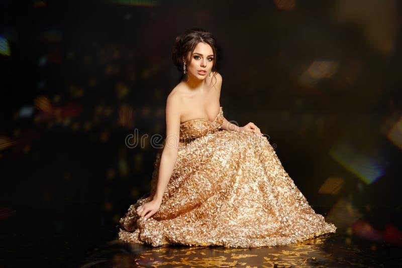 Härlig sexig och glamorös brunettflicka i en guld- klänning Blac fotografering för bildbyråer