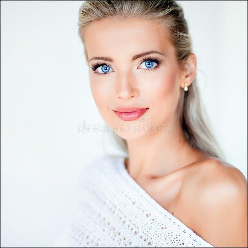 Härlig sexig sinnlig blond flicka i ett vitt omslag i studio, arkivfoton