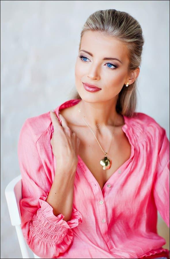 Härlig sexig sinnlig blond flicka med blåa ögon i en rosa stålar royaltyfri fotografi
